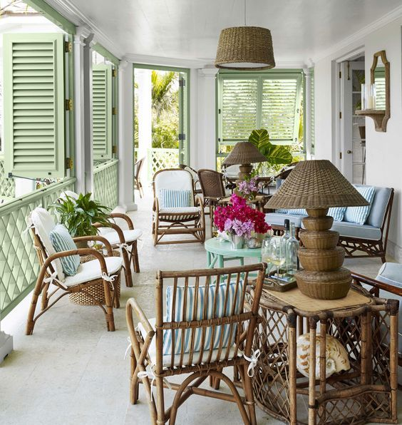 a stylish veranda with rattan chairs, a blue table and a sofa, a rattan table and a wicker lamp plus green shutters on the windows
