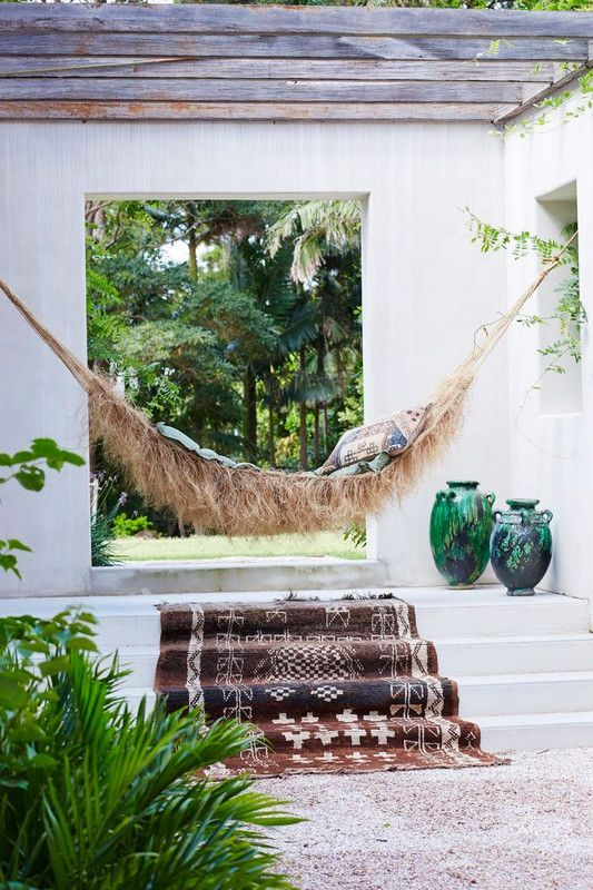 a patop with a roof, a woven hammock that looks really wild, with printed textiles and potted greenery and vases