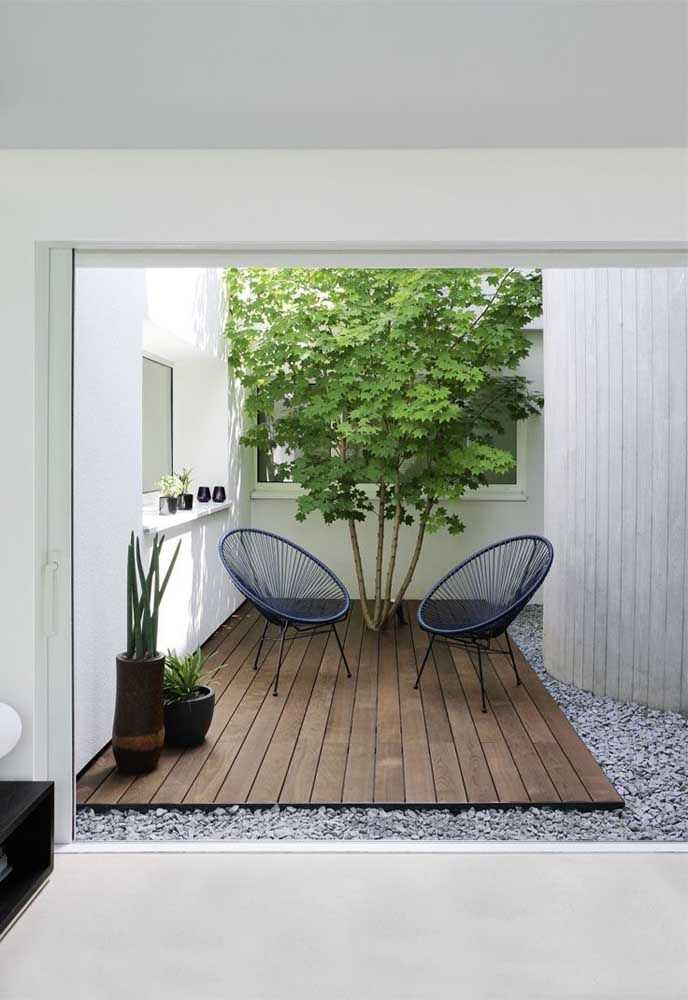 a small modern backyard with a wooden deck, navy woven chairs, a living tree and some potted plants is cool and chic