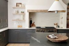 29 a sophisticated kitchen with grey cabinets and a black marble kitchen island, a hood that matches a backsplash and open shelves