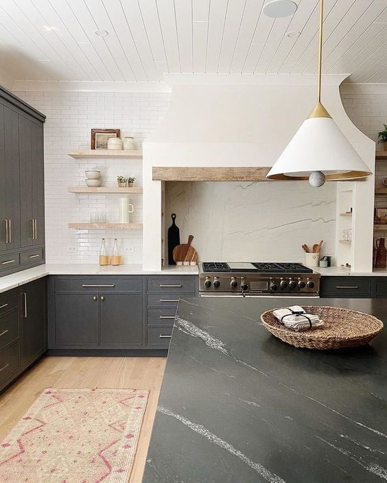 a sophisticated kitchen with grey cabinets and a black marble kitchen island, a hood that matches a backsplash and open shelves