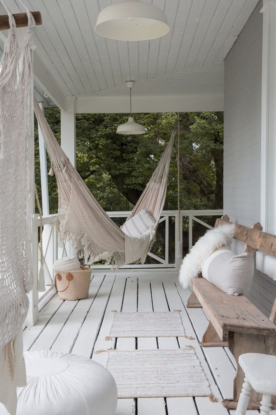 a relaxed boho porch with a planked floor, a hammock, a bench with pillows, poufs and macrame is a chic idea