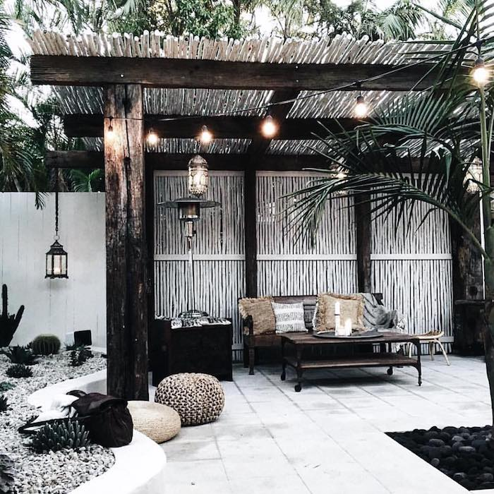a small tropical backyard with a gazebo, an upholstered bench and a low table, a chest for storage, string lights and pretty poufs