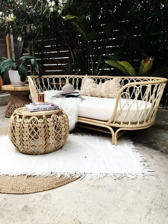 a tropical outdoor space with a rattan daybed, a rattan pouf and a side table, layered rugs and tropical plants around