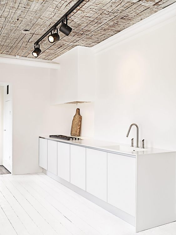 an airy white minimalist kitchen with sleek cabinets and a white hood that merges with the wall and is almost invisible
