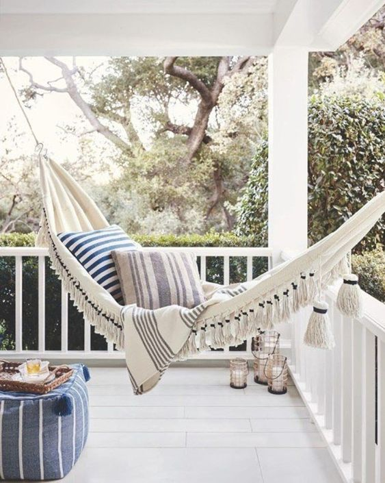 a relaxed coastal porch with a hammock with tassels and printed pillows, a striped pouf and candle lanterns in the corner