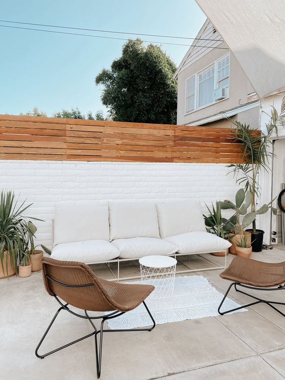 a stylish contemporary backyard with some potted cacti and succulents, with a neutral sofa, wicker chairs and a small side table