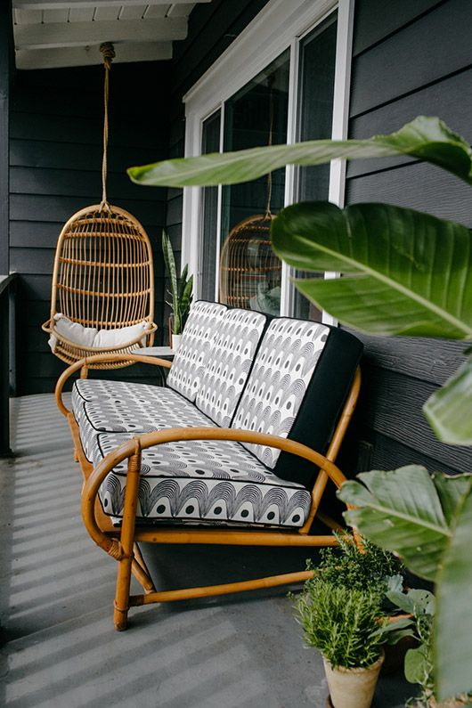a tropical porch with a rattanegg-shaped suspended chair and a rattan sofa with printed cushions plus greenery around