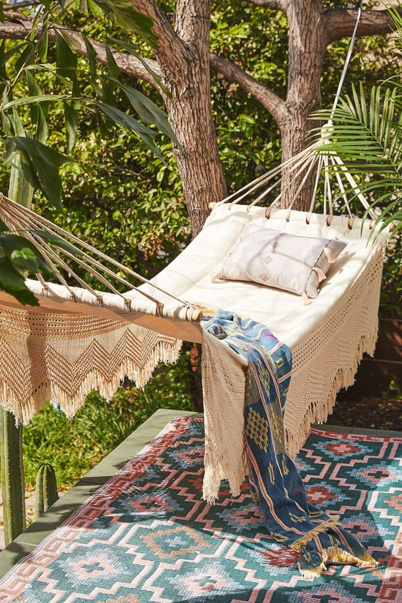 a small and cozy outdoor space with a hammock attached to the trees and colorful boho textiles is very welcoming