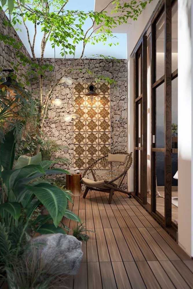 a tiny refined backyard with a wooden deck, tall stone walls and mosaic tiles for decor, a woven chair and some cool plants and trees