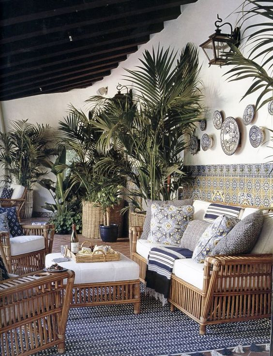 a tropical terrace with rattan furniture, printed pillows and blankets, potted plants, mosaic tiles, a printed rug and some lamps
