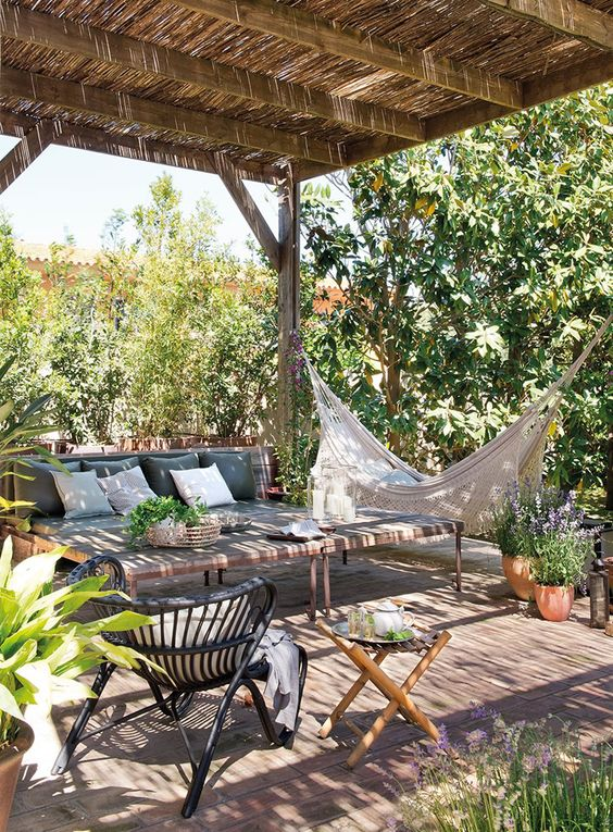 a terrace with a roof, rattan and wooden furniture, a hammock, two low coffee tables and potted greenery is a chic space