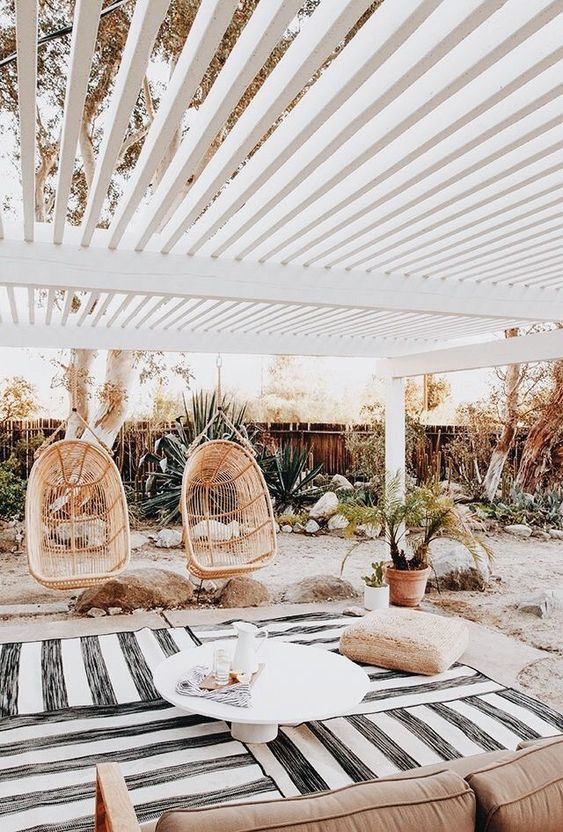 a tropical terrace with striped rugs, a soft sofa, a jute pouf and a coffee table plus a potted plant and two egg-shaped rattan chairs