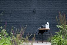 a Nordic outdoor shower with a black brick wall, a small stool with towels and shampoos, a wooden deck