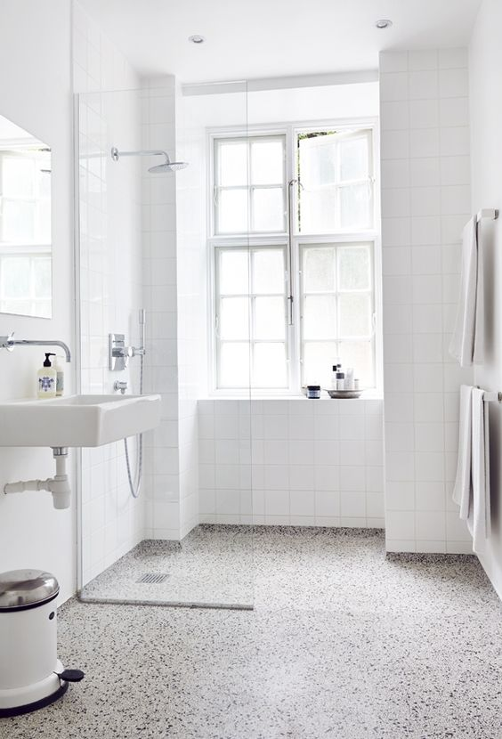 a Scandi bathroom with white square tiles and a black and white terrazzo floor, white appliances and a large window