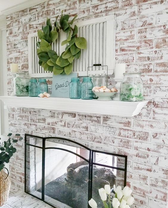 a beach farmhouse mantel with a foliage wreath, turquoise jars, jars with sea glass and some seashells is cool and cozy