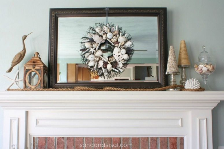 a beachy mantel with a seashell and starfish wreath, a wooden candle lantern and a rope, seashells in a jar