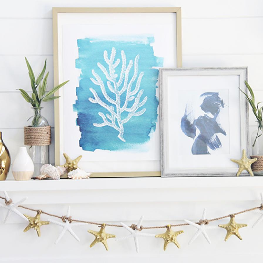 a beachy mantel with a starfish garland, seashells and starfish on it, pretty watercolors and some greenery