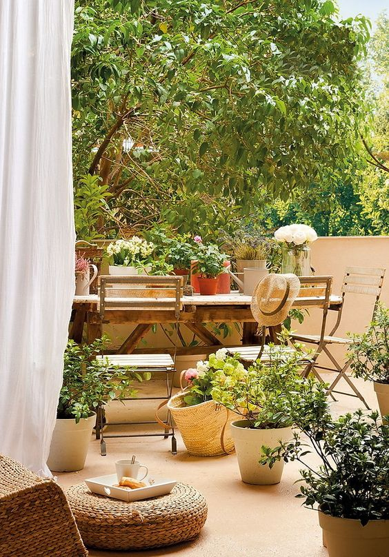 a beautiful Mediterranean terrace with a simple woodne dining seat, potted plants and blooms, a jute pouf is very welcoming