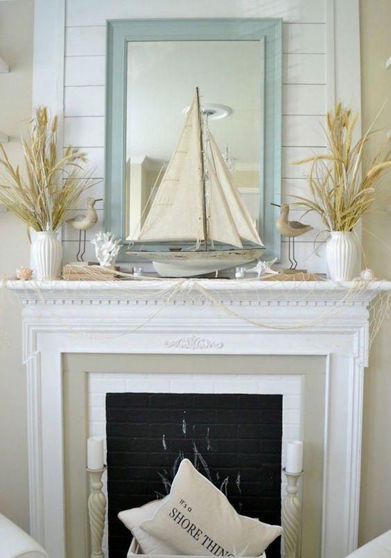 a beautiful coastal mantel covered with net, with corals and starfish, vases with pampas grass and a boat plus a mirror in a light blue frame
