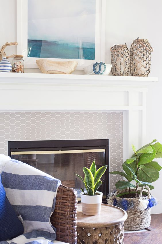 a beautiful coastal mantel with a watercolor artwork, lanterns wrapped with rope, a jar with seahshells, driftwood and a bowl with blue beads