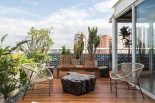 a beautiful contemporary rooftop terrace with a wooden deck, concrete loungers and cool chairs, a wooden bench and potted trees and plants