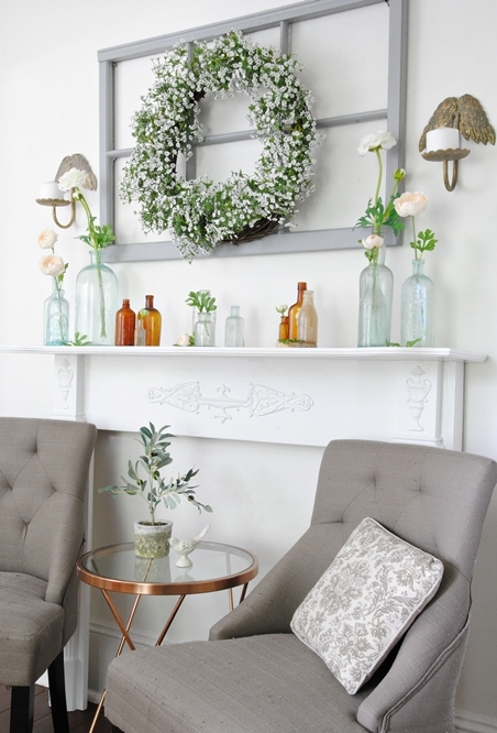 a beautiful summer mantel with a white bloom and greenery wreath, a window frame, bottles and vases and wall sconces
