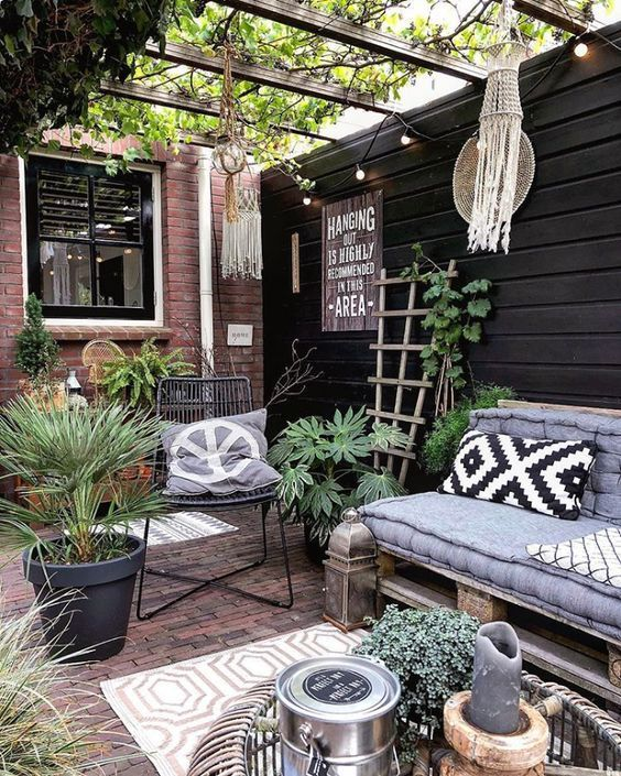 a boho summer patio with a brick floor, layered rugs, a pallet loveseat, a rattan table, potted greenery and candle lanterns and macrame decor