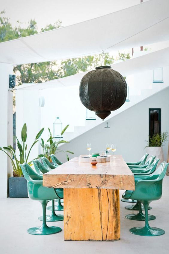 a bold contemporary dining room with a wooden table of several slabs, bold and shiny green chairs and a black metal pendant lamp