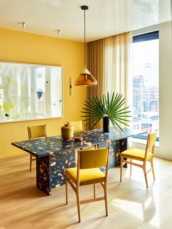 a bold dining room with a yellow accent wall, a terrazzo dining table, yellow chairs and curtains plus a yellow and amber pendant lam[