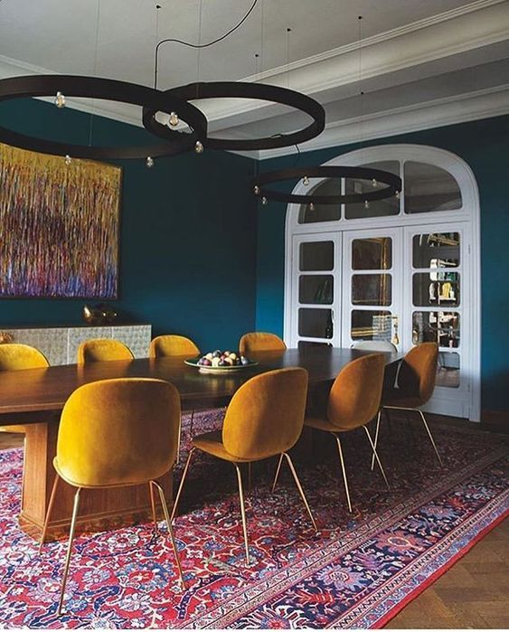 a bold modern dining room with teal walls, a long table, mustard velvet chairs, a printed rug and ring chandeliers