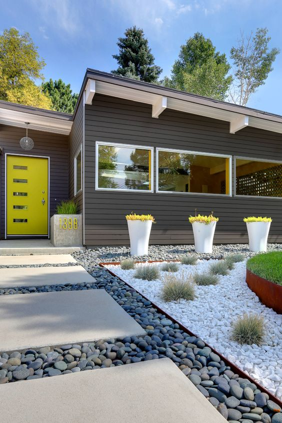 a bright and cool modern front yard with pebbles, tiles, grass balls and bold greenery in tall planters plus a planter with a neon house number