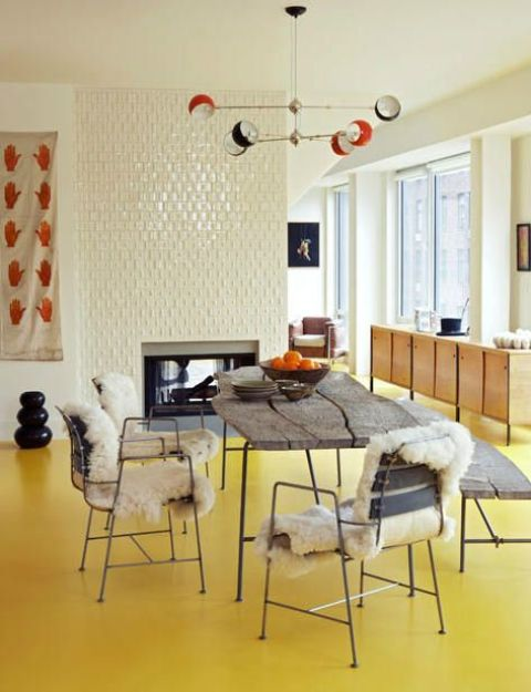 a bright and fun dining room with a sunny yellow floor, a fireplace clad with tiles, a rough wood dining table and chairs