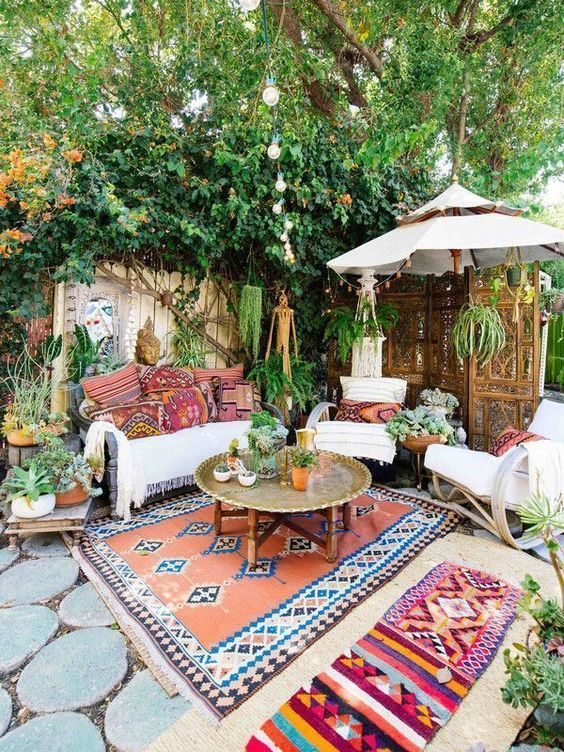 a bright boho summer terrace with a white sofa, printed pillows, rockers, printed rugs, a metal table and potted greenery and plants