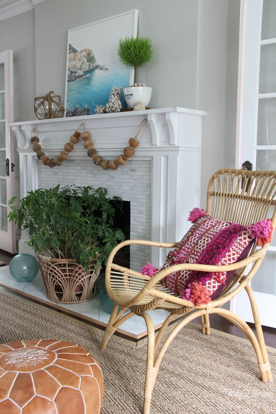 a bright coastal mantel with a wooden bead garland, a potted plant, some seashells, a buoy and a bright photo of the coast