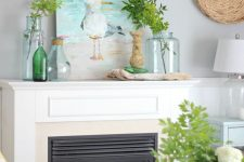 a bright coastal mantel with greenery in jars, green bottles and driftwood, a sea gull artwork as a centerpiece is chic