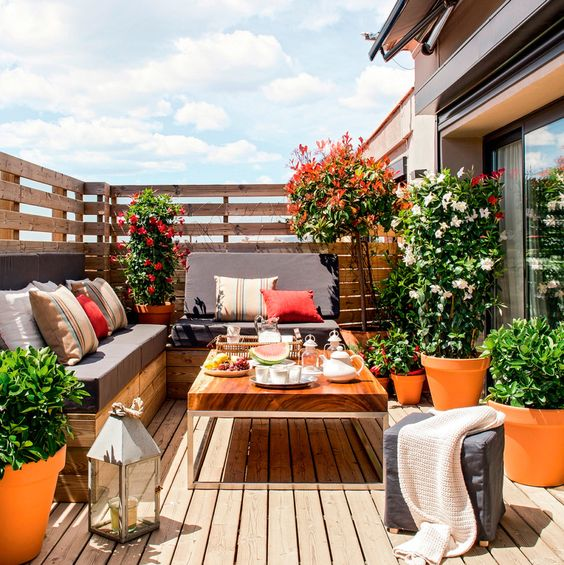 a bright modern rooftop terrace with a sectional, a low coffee table, potted plants and blooms and a candle lantern