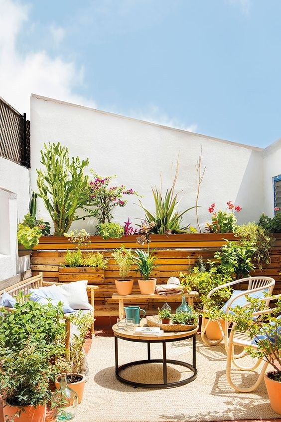a bright summer terrace with a bench with pillows, rattan chairs, a round table, potted plants and blooms is a very cool idea