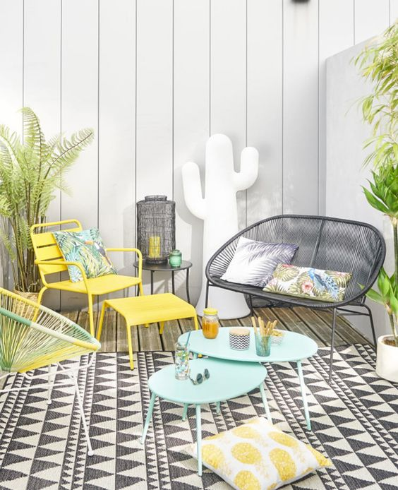 a bright summer terrace with a printed rug, turquoise, yellow and black woven furniture, potted plants and printed pillows is welcoming