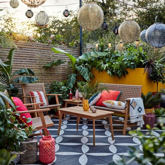 a bright tropical terrace with a mosaic tile floor, cane and wood furniture, bright pillows, lanterns over the space and tropical plants