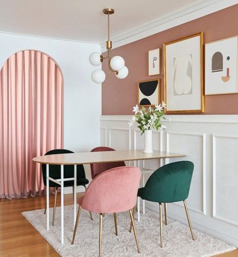 a catchy pink dining space with a mauve and white panel accent wall, pink curtains, an oval table with green and pink chairs