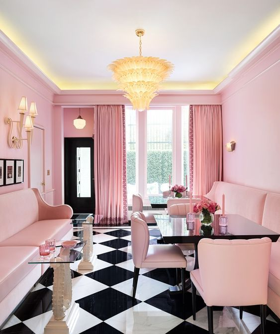 a catchy retro-inspired pink dining room with pink walls, sofas and chairs, with a gorgeous chandelier, a checked floor and elegant glass side tables