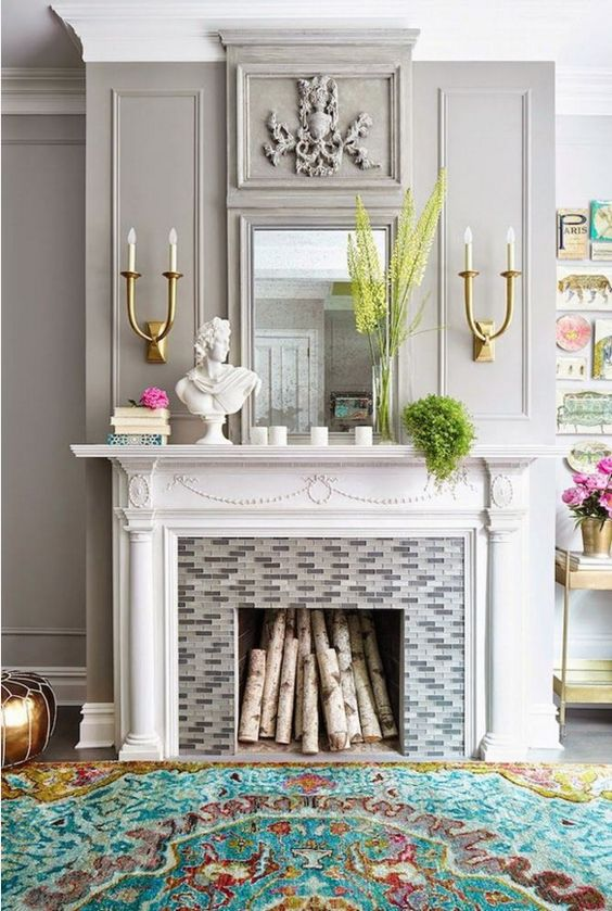 a cheerful summern mantel with greenery and bold blooms, candles, a stack of books and a statuette