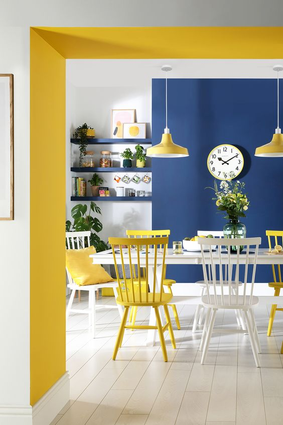 a chic and bold dining room with a navy wall, a yellow ceiling, chairs, pendant lamps and pillows plus navy built-in shelves