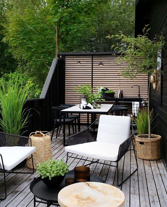 a chic and lively Scandinavian summer terrace with black and white furniture, a small kitchen countertop with a sink, a dining and sitting space