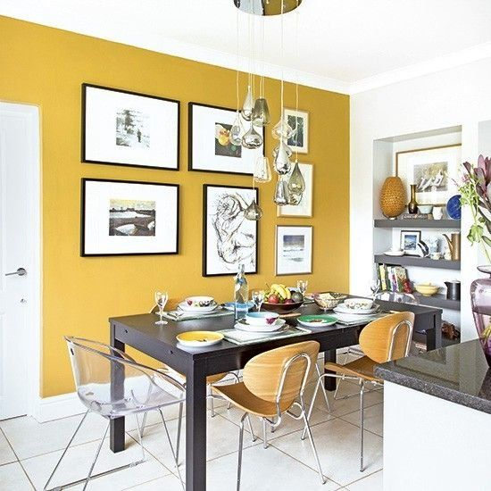 a chic and refined dining room with a mustard accent wall, a black table and mismatching chairs, a cluster of pendant lamps