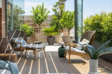 a chic and stylish rooftop terrace with a slight planked roof, potted plants and trees, rattan and woven furniture and a low coffee table