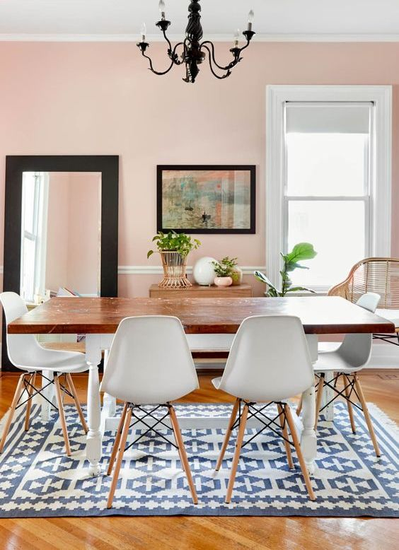 a chic dining space with blush walls, a floor mirror, a vintage dining table and white chairs plus a vintage black pendant lamp