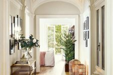 a chic hallway with white walls and arched ceilings, with light-stained hardwood floors and lovely gallery walls