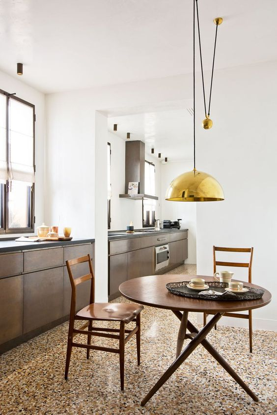a chic kitchen with a bright and warm-colored terrazzo floor, dark stained cabinets, a rich stained dining set and gold touches